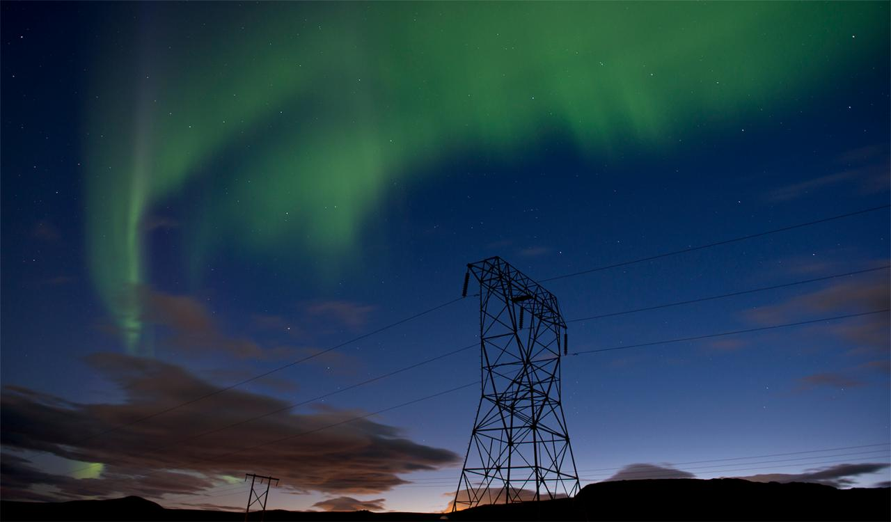 Power lines at night with the aurora borealis