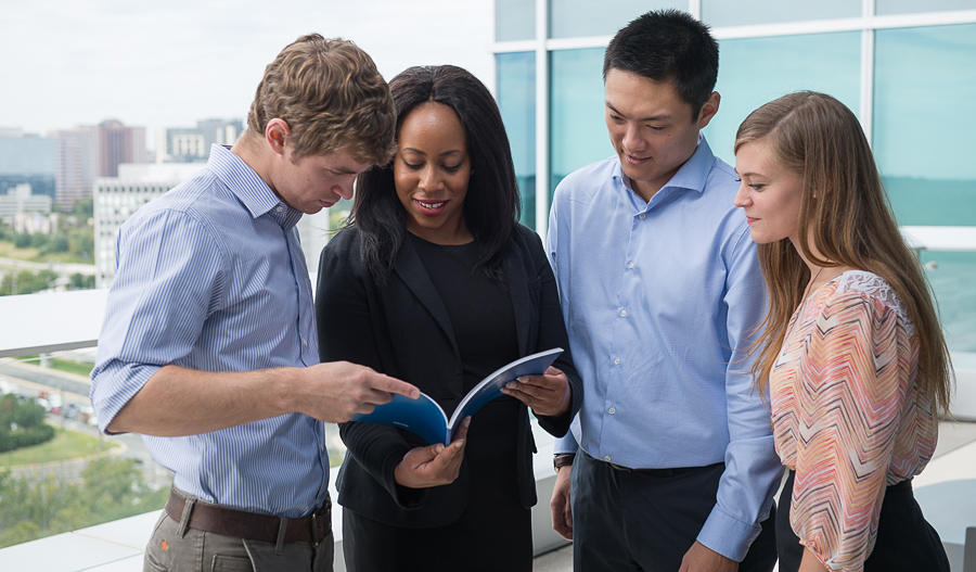 Employees looking at a report outdoors.
