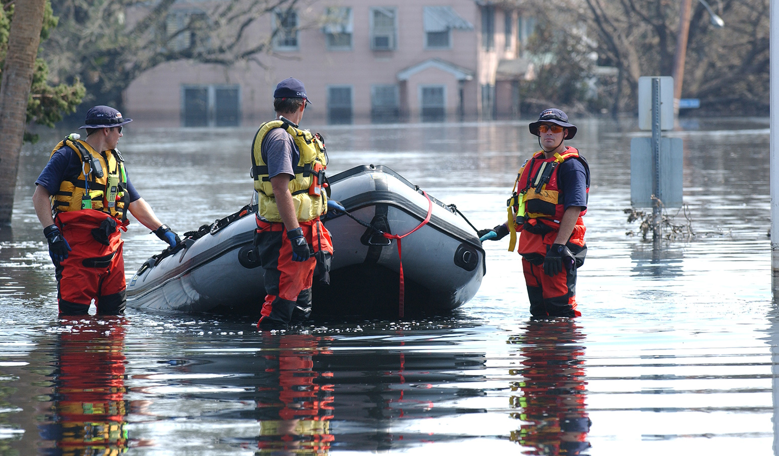 Three emergency personell pull dingy through flooded street