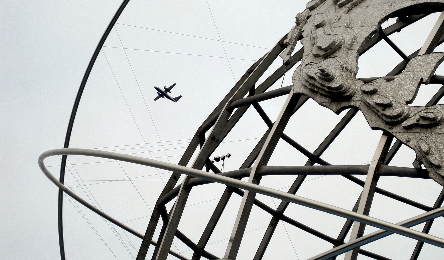 Metal sculpture of the globe frames aircraft's flight in gray skies.