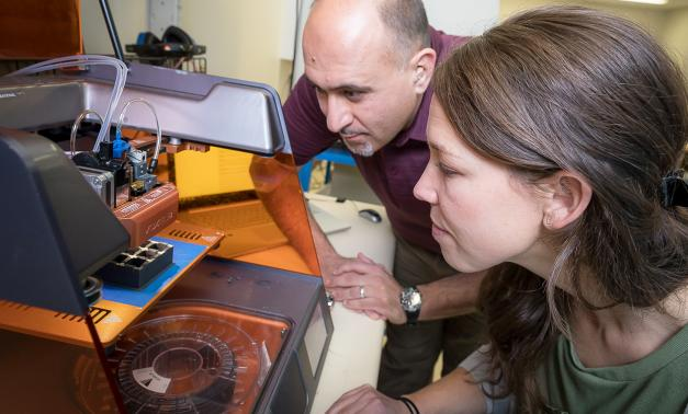 Employees looking at 3D printer