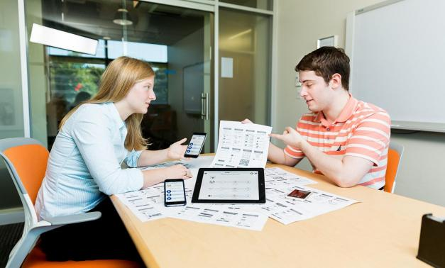 MITRE staff Lindsay Kaye and Adam Holmes review plans for the BrainKit TaskPlanner app.
