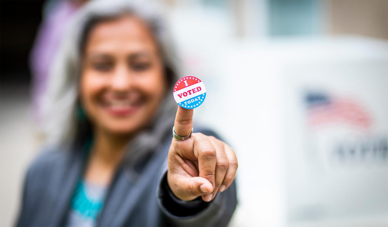 Woman holding an I Voted sticker