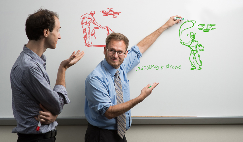 Two researchers use a whiteboard to illustrate their ideas.