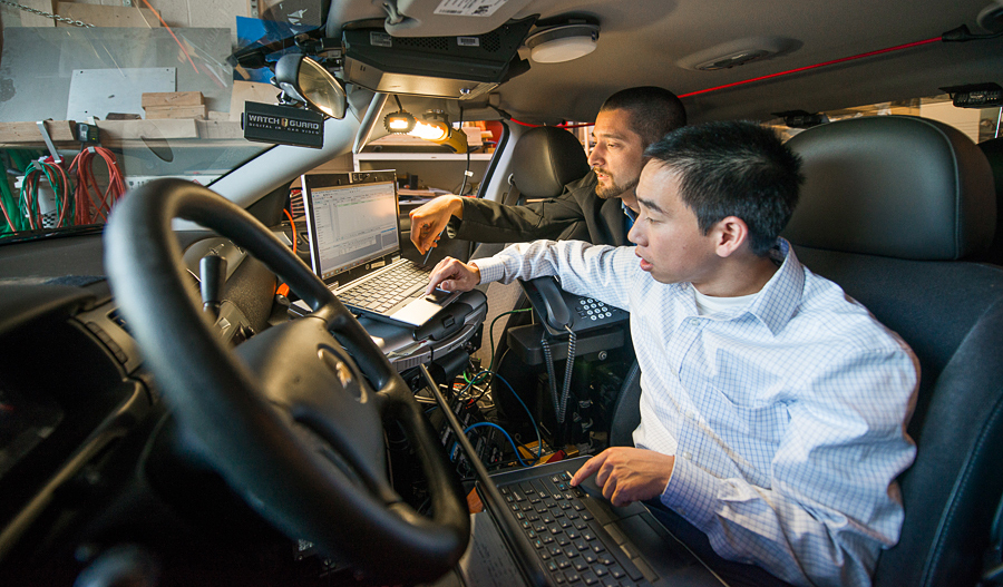 Researchers in a police car