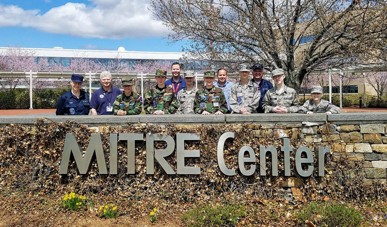 Student Cadets behind MITRE Center sign