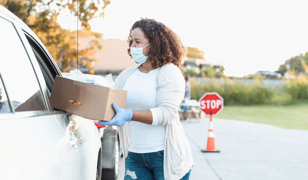 Masked female volunteer handing over a box of food to person in a car.