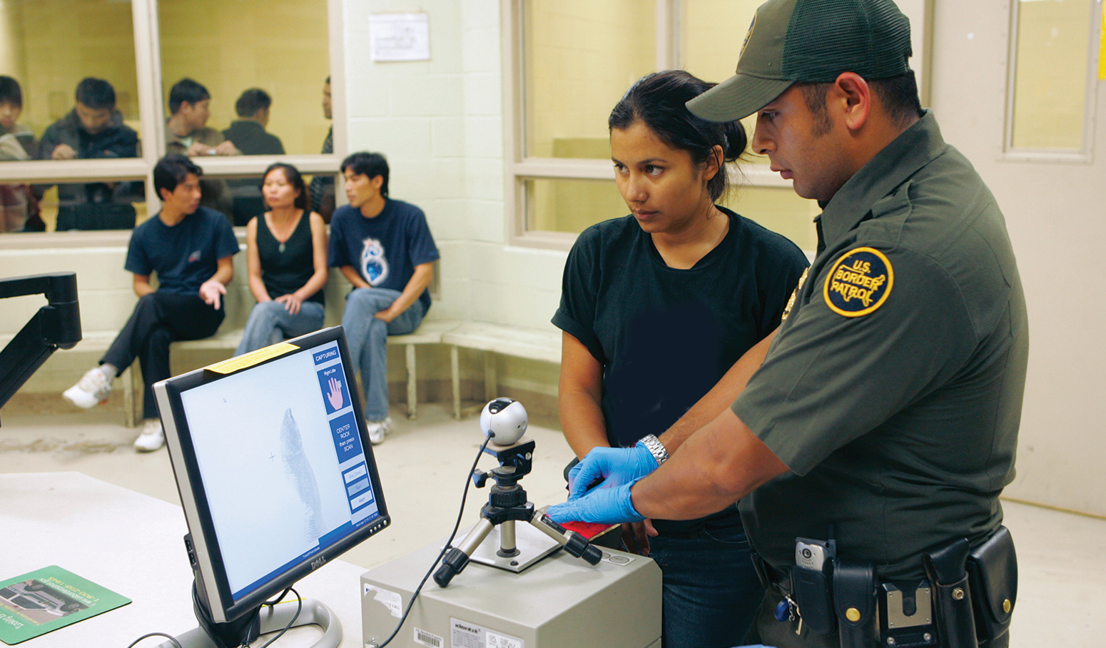 Woman's fingerprints being captured digitally by border patrol agent