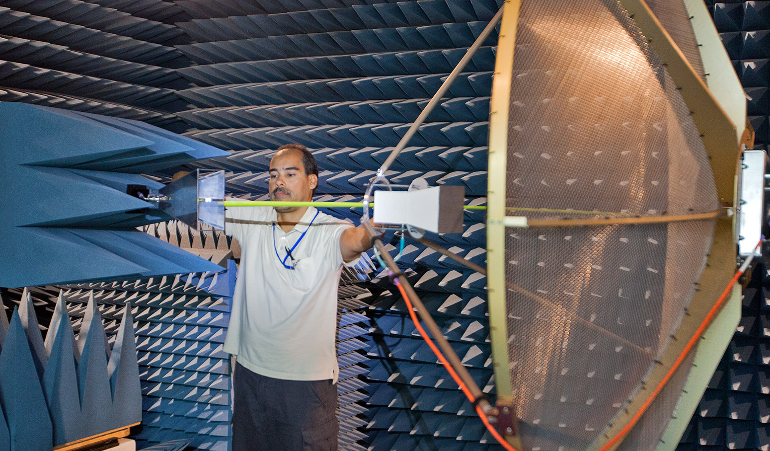 man adjusting sophisticated equipment in anechoic chamber