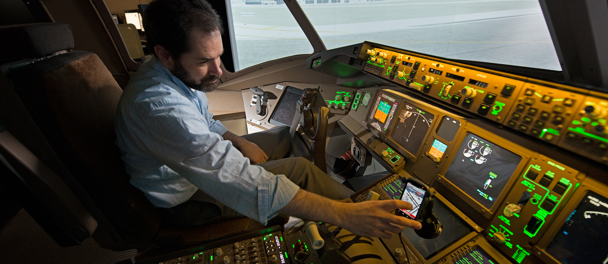 Pilot views aircraft position on runway on mobile device screen.