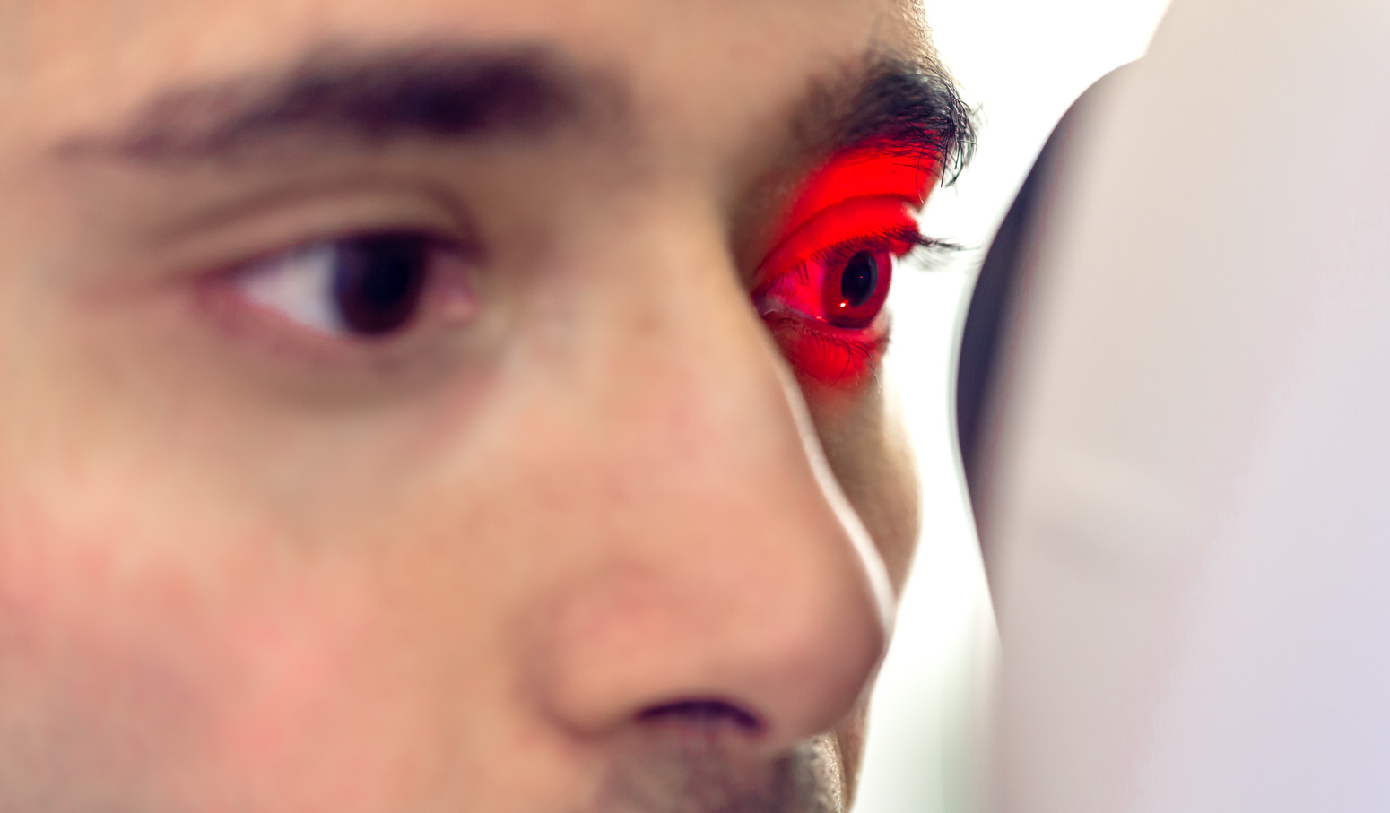 Close up of two eyes. One is encircled by red light from machine that is being looked into.