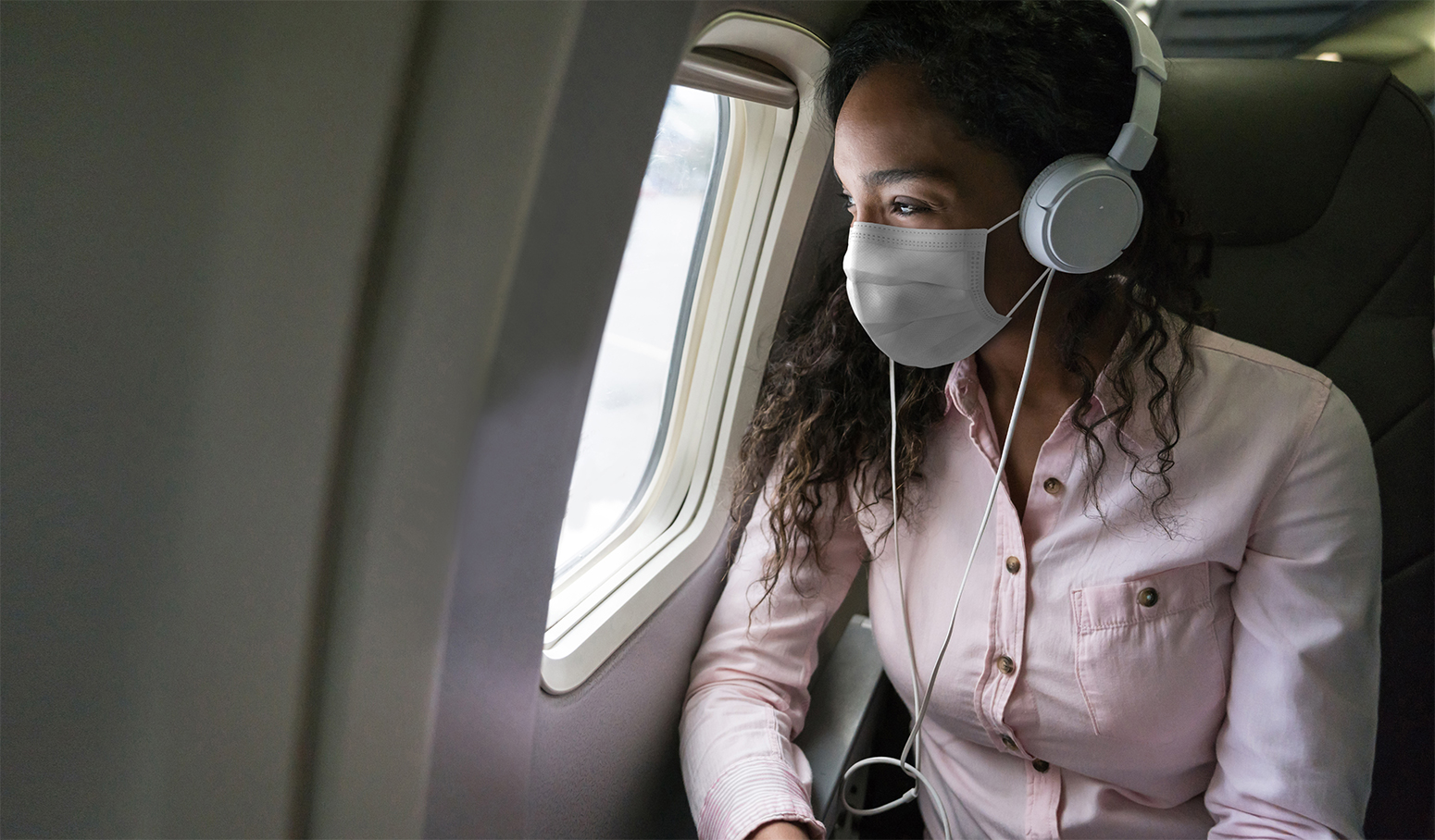 Woman wearing a mask on an airplane