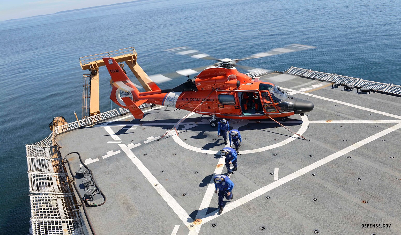 Coast Guard new members exit from an MH-65 Dolphin helicopter