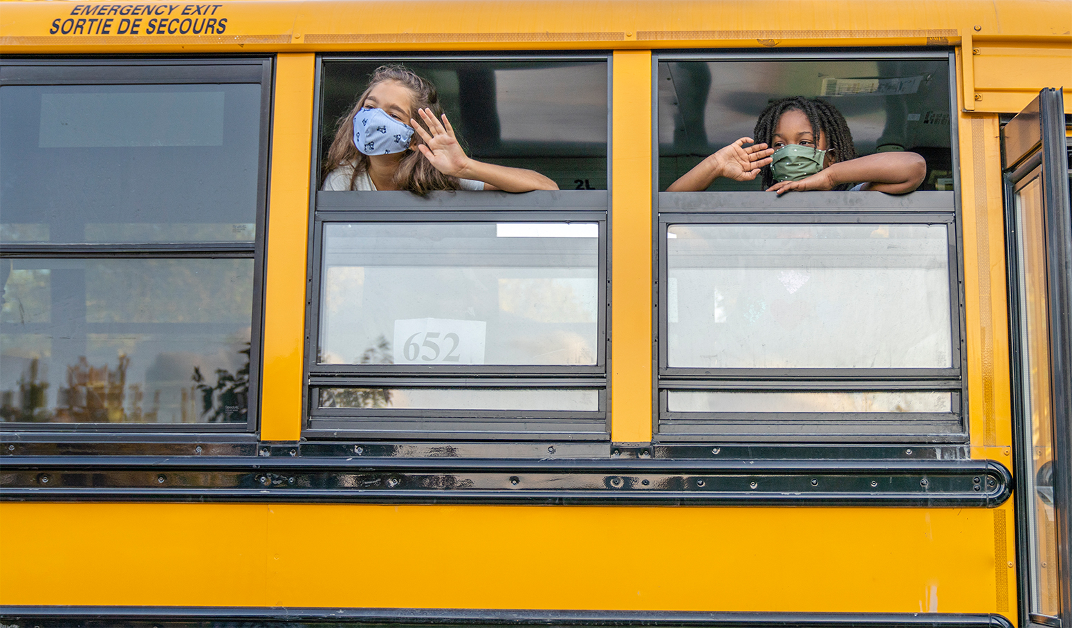 Children in masks at the open windows of a school bus