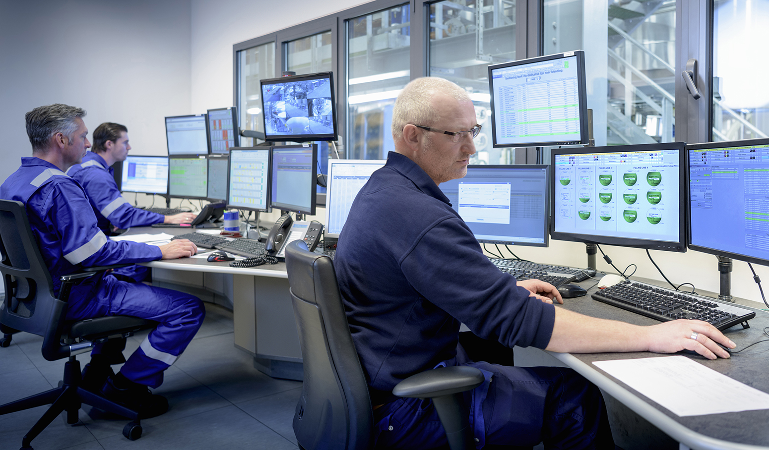 Workers in a control room surrounded by computer monitors.