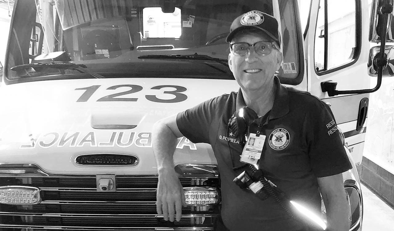 Volunteer paramedic Dennis Popiela standing in front of an ambulance