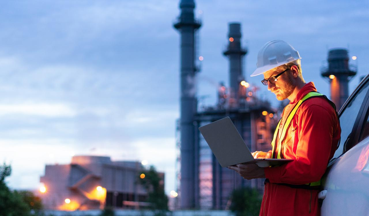 An engineer, wearing an orange safety vest, working on a laptop outside a power plant