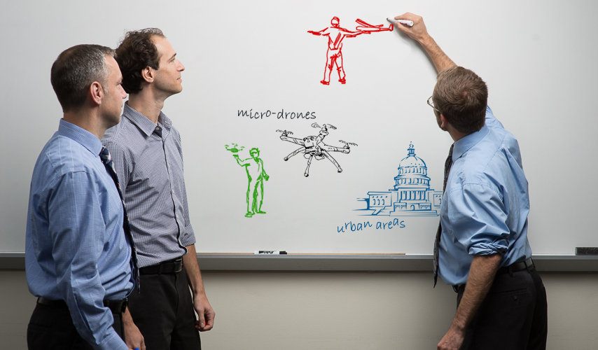 Three researchers use a whiteboard to illustrate their ideas about unauthorized drones.