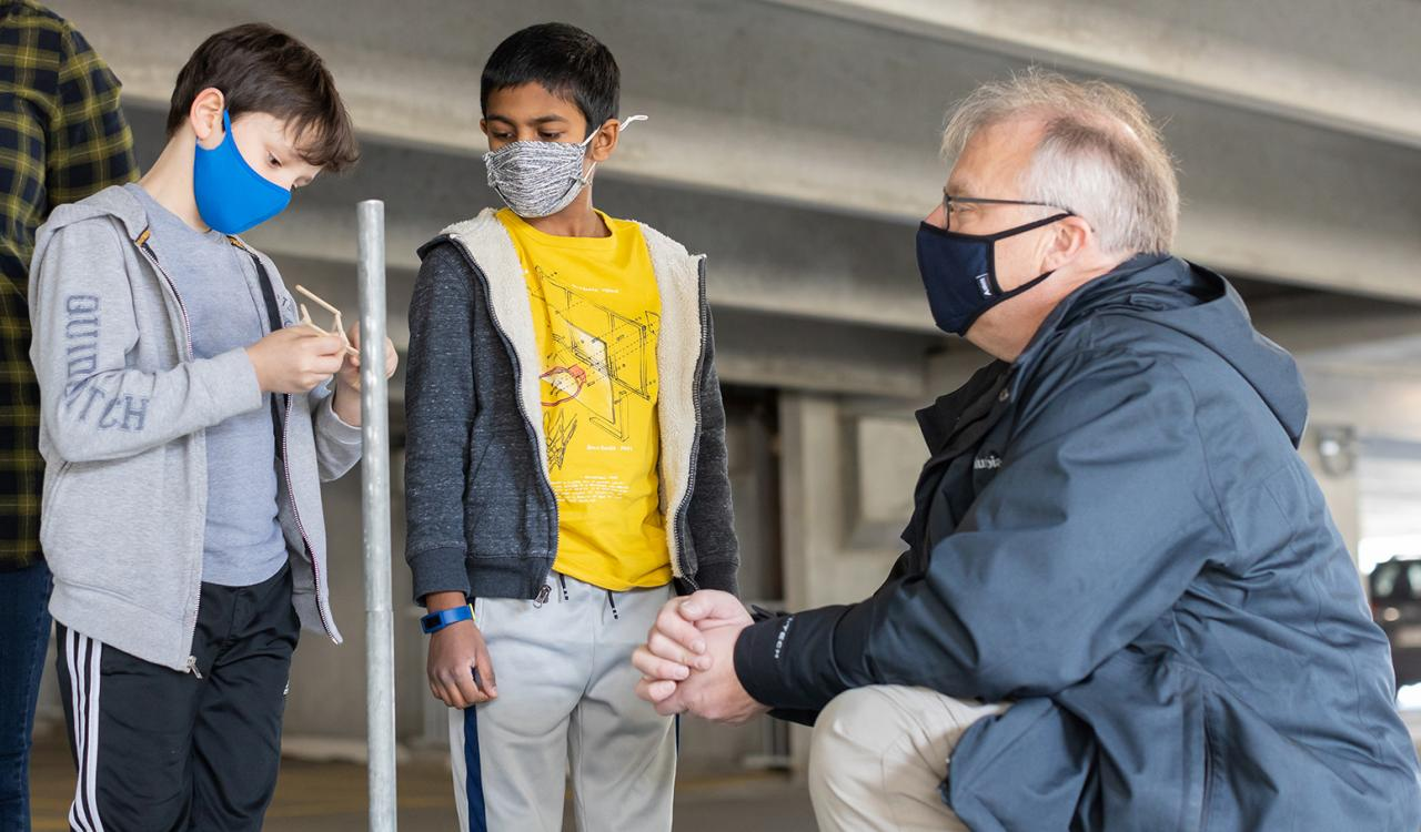 Students from Sangster Elementary School in Springfield, Virginia, examine a piece of their balsa structure with MITRE's Robert Kobee at the Odyssey of the Mind Northern Virginia chapter tournament this spring. Photo by Julian Nguyen.