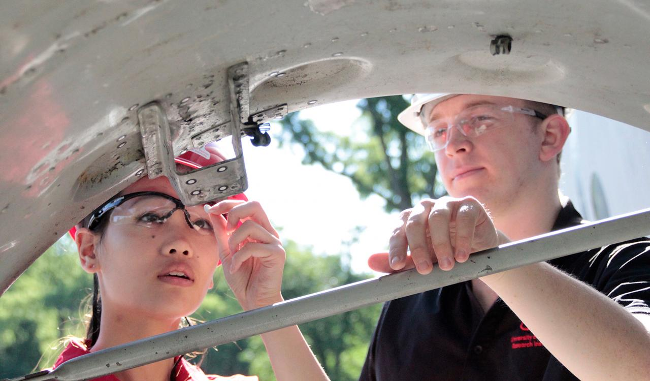 Two researchers at UDRI wearing hard hats inspecting a project.