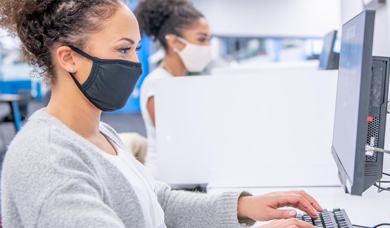 Two college students wearing masks working side by side with divider between them.