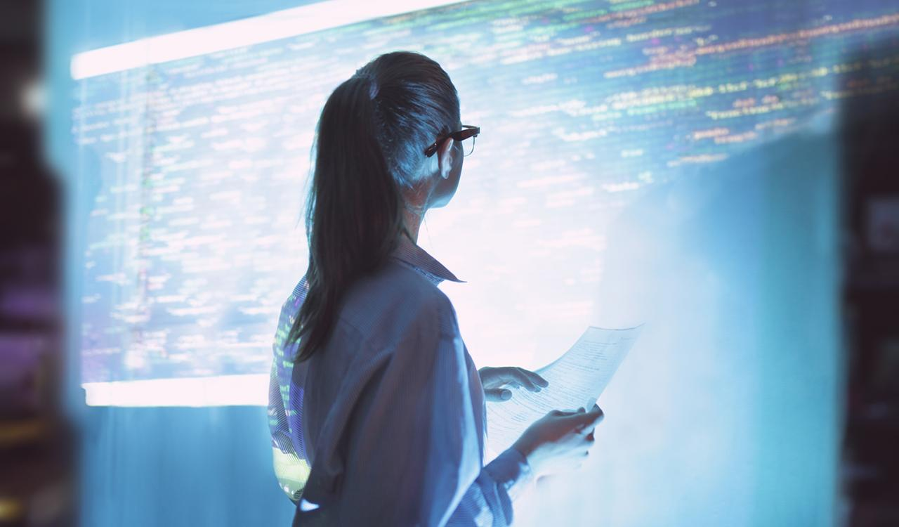 Woman looking at large screen covered in data