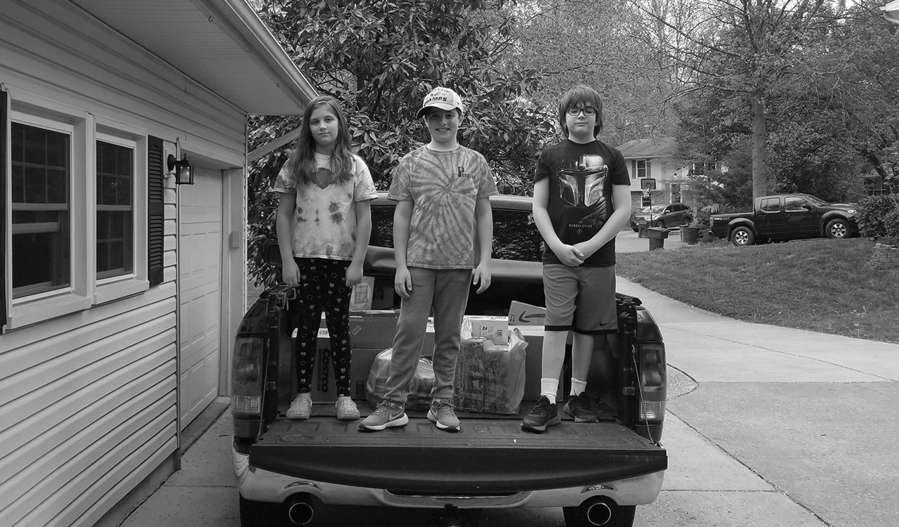 Children standing in the bed of a truck filled with donations