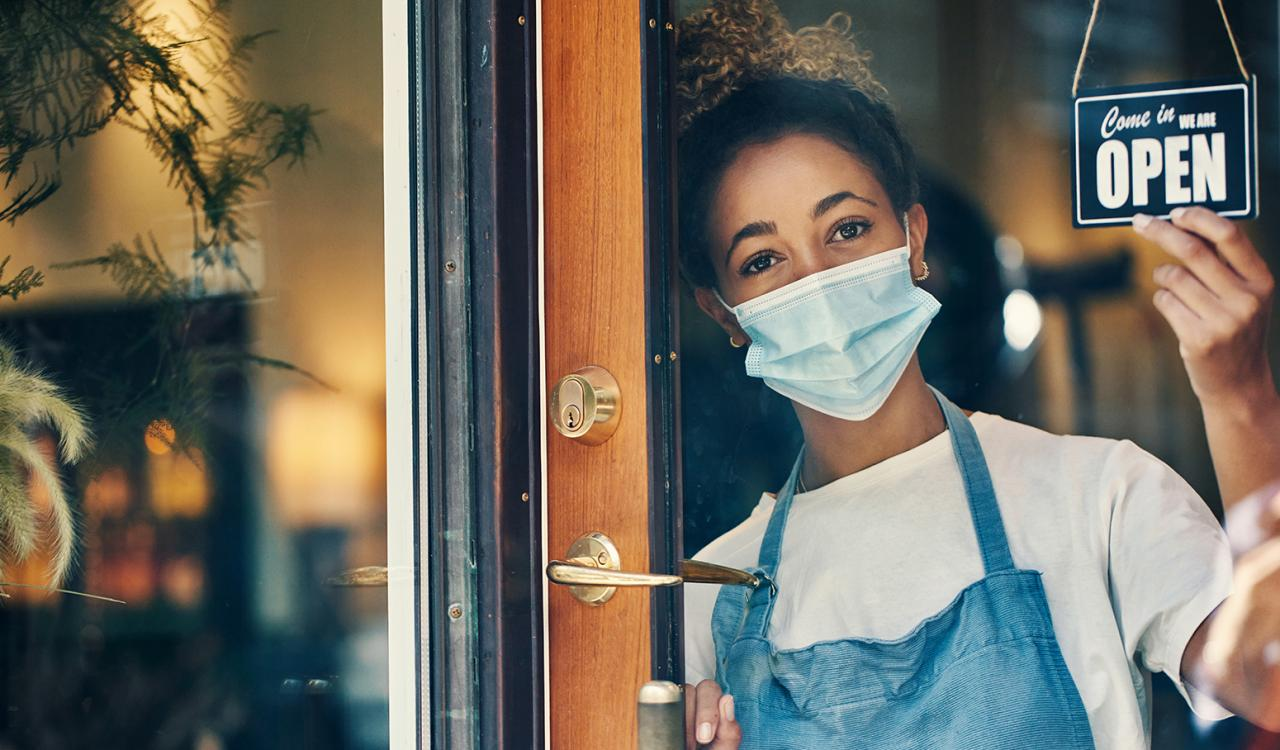 Masked business owner opening her store for the day