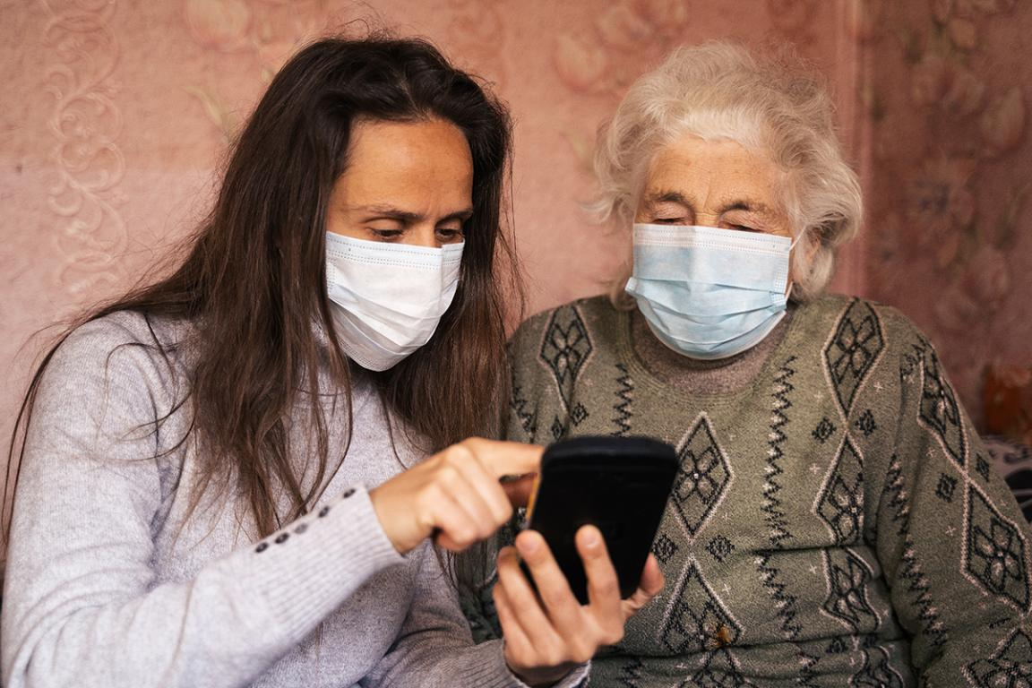 A woman showing an elderly woman something on her phone, both wearing masks