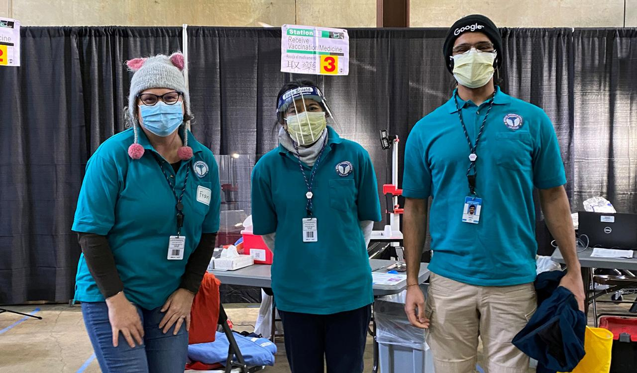 Three volunteers at the vaccination clinic wearing full PPE and beanies to keep warm