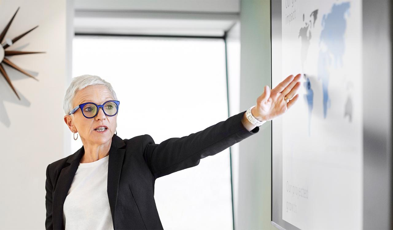 A women in a blazer and purple glasses gesturing to a global map