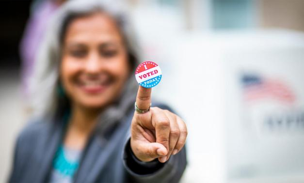 Woman pointing with I voted sticker on her finger