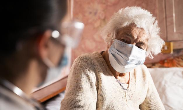Elderly resident of nursing home wearing a mask and talking to a medical caregiver.