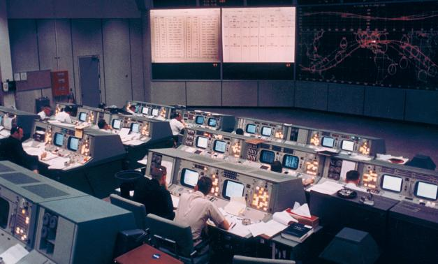 Houston control room before Apollo mission with computers and video screens.