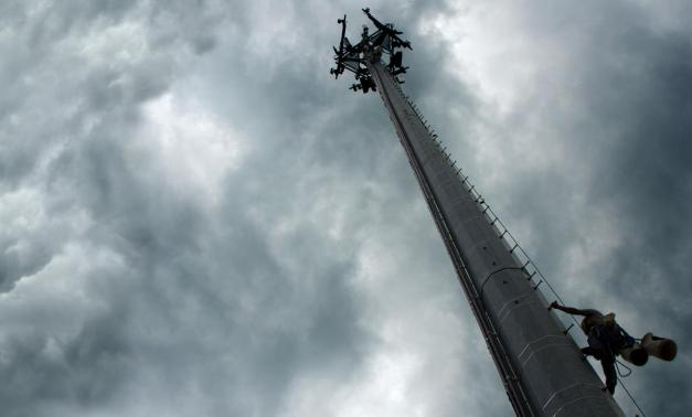 5G cellular tower in front of cloudy skies