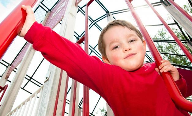 Child in red shirt climbing on a play structure