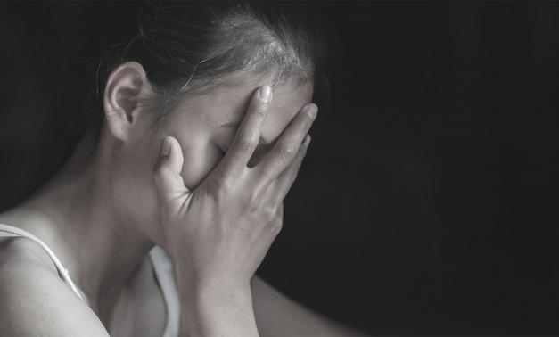 Upset woman with her hand covering her face
