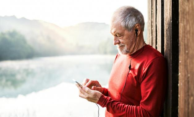 Senior man with smartphone and earphones outdoors