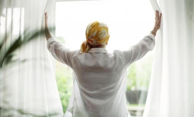 Woman opening curtains in front of a window