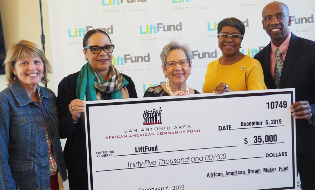 Members of LiftFund smiling and holding a large check for $35,000