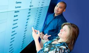Two co-workers look at a wall-sized screen full of data to analyze it.