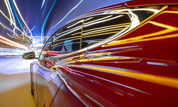 Lights reflected off of a car as t travels at a high rate of speed