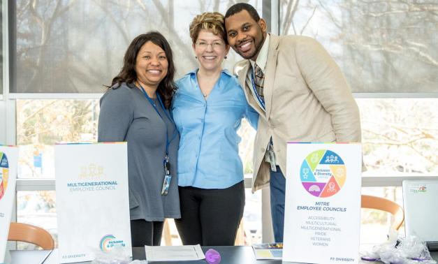 Three employees posing at the employee council fair
