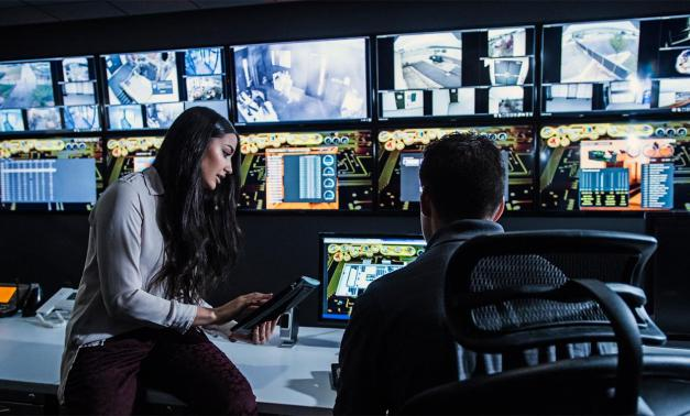 Woman and man in a security control room surrounded by video monitors.