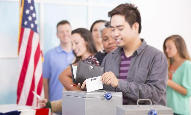 Voters putting ballots in box in front of American flag