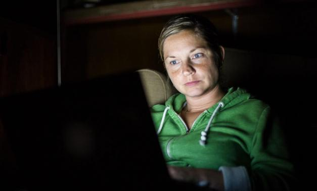 A woman wearing a green hoodie using her laptop in the dark