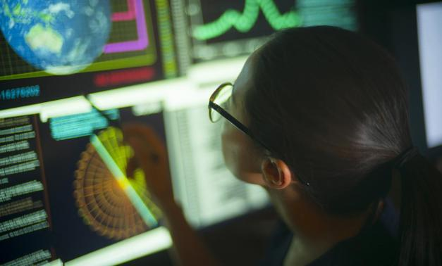 Woman in front of multiple computer screens with data.