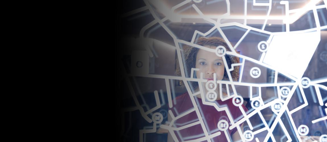 Woman standing in front of map on a glass screen