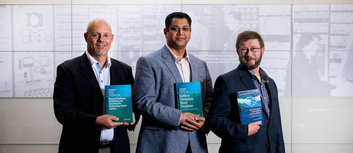Ernie Page, Saurabh Mittal, and Andreas Tolk holding their books