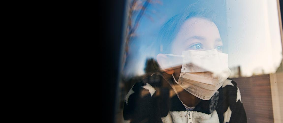 Young girl wearing a mask, looking out a window